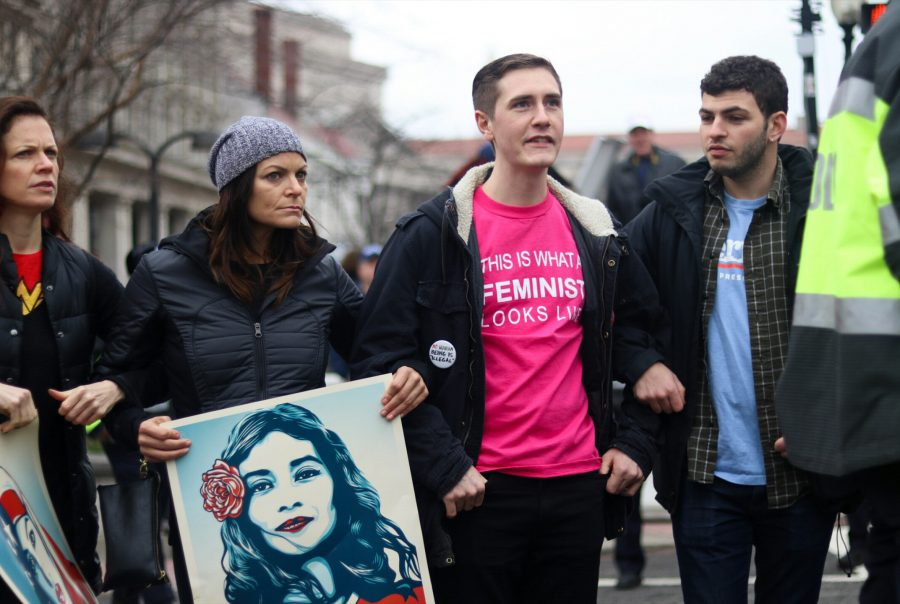 Women+and+men+supporting+the+March%2C+holding+artist+Shepard+Fairely%27s+%22We+the+People%22+portraits+and+wearing+a+feminist+shirt.+