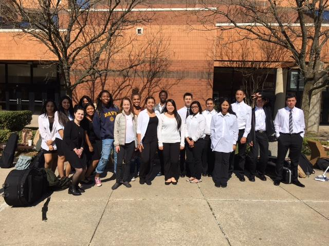 The orchestra poses after festival at Quince Orchard High School