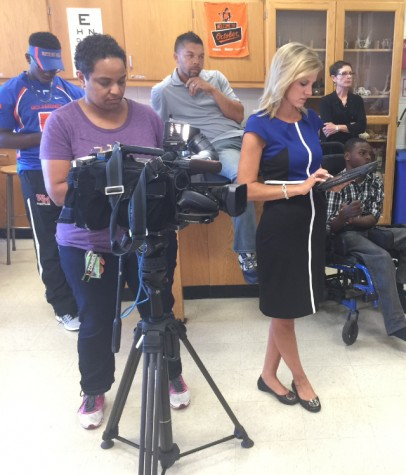 """Watkins Mill staff members look on as NBC4's Melissa Mollet films an interview for her segment on the """"Chair4Ibra"""" fundraiser"""