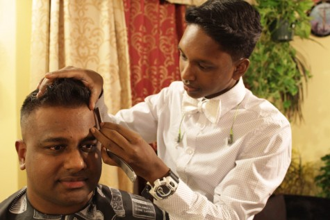 Senior Glen Gabriel lines up pilot Ravi Cherian's hairline.