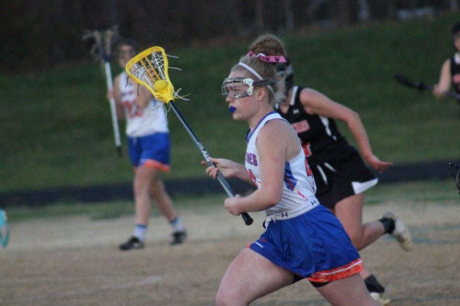 Sophomore+Virginia+Schlosser+runs+the+ball+down+the+field