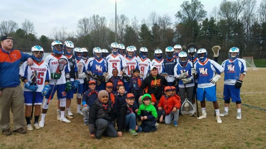 Boys+varsity+lacrosse+poses+with+coach+Jordan+Montesano+and+local+Boy+Scouts