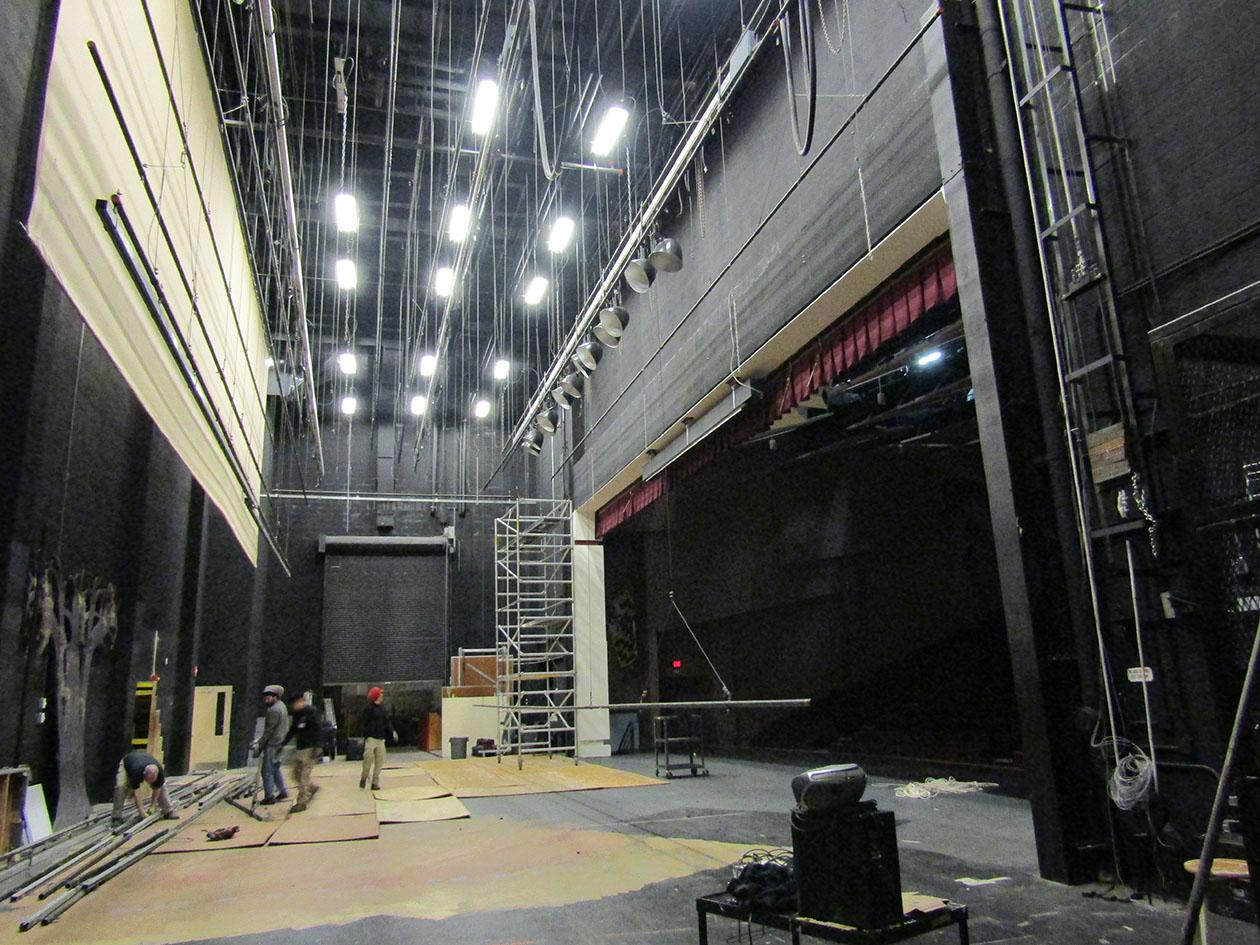 Workers begin construction on the new stage rigging.