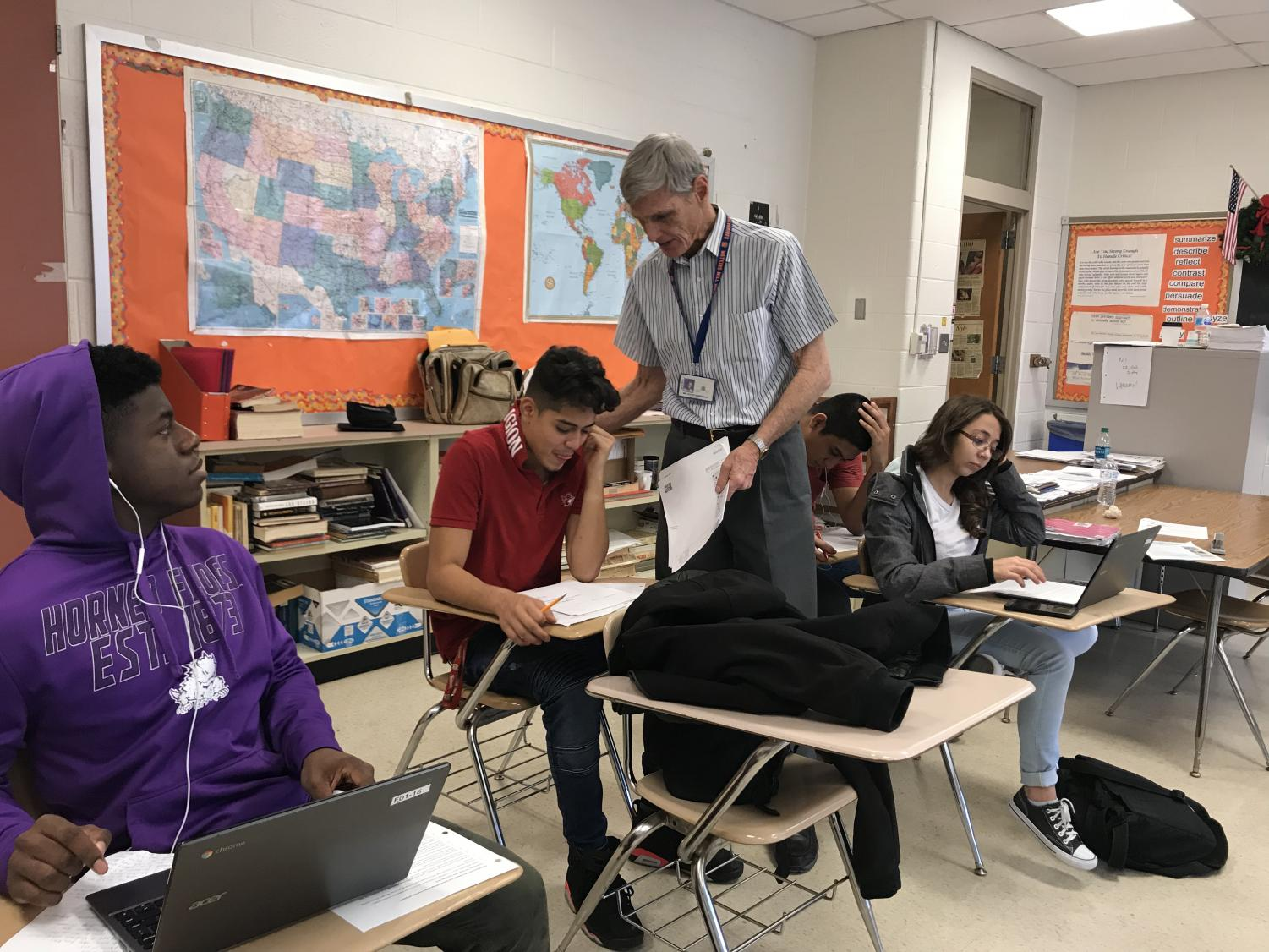 English teacher David Sampselle helps senior Jeff Flores with an assignment