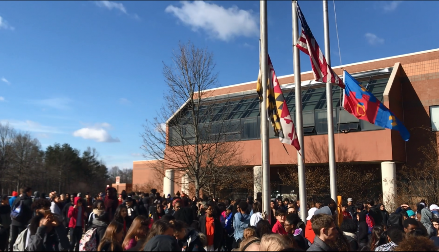 Students+gathering+at+the+flag+poles+for+the+school+walkout.