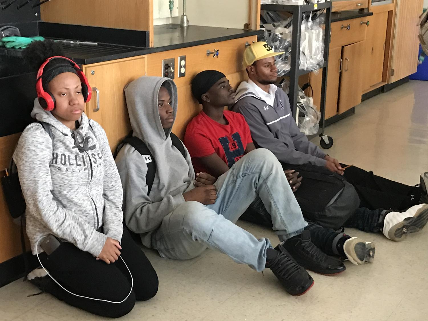 Students sit silently against the wall during the active-shooter drill