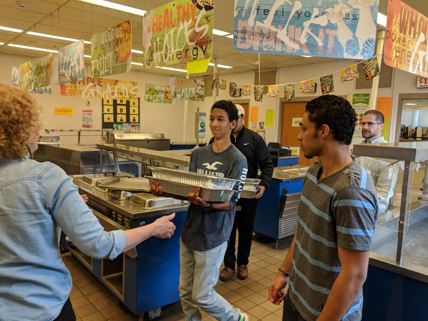 Sophomore Fahad Habona and senior Ravi Bullard serve lunch for the building services team