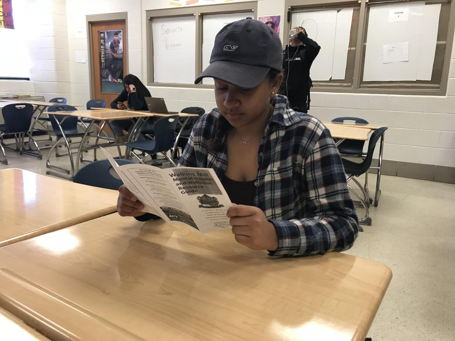 Senior Christina Cordero reads through the suicide prevention brochure in her math class