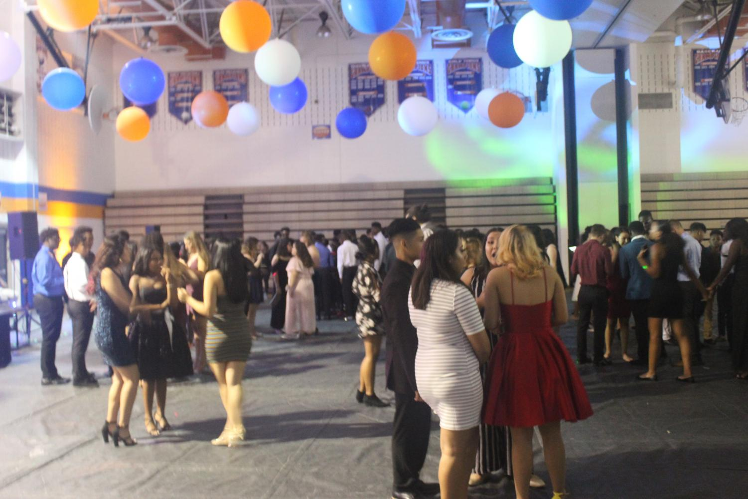 Students stand around with friends on the dance floor.