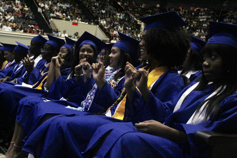 Graduating alumni smiling with joy during graduation.