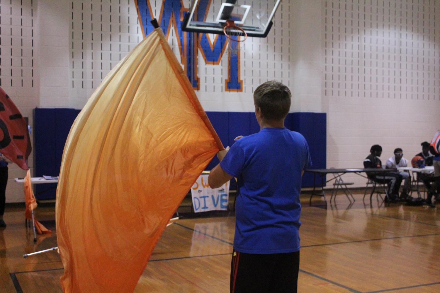 Junior+Ryan+Pranger+practices+with+his+flag+for+marching+band+before+the+Extracurricular+Activities+Fair.