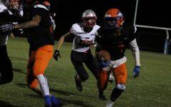 Junior Darnell Lewis Jr. runs the ball down the field, moving past a Blair football player.