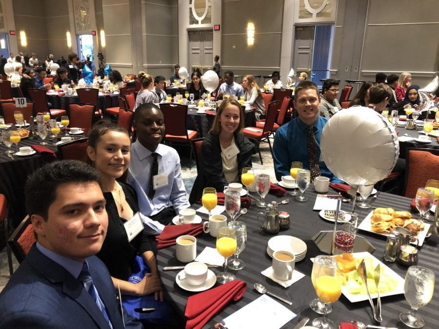 Seniors Richard Epperly, Adaly Ascencio, Francis Eseh and Nadia Makmak sit with science resource teacher Matt Reese at the Superintendent's breakfast.