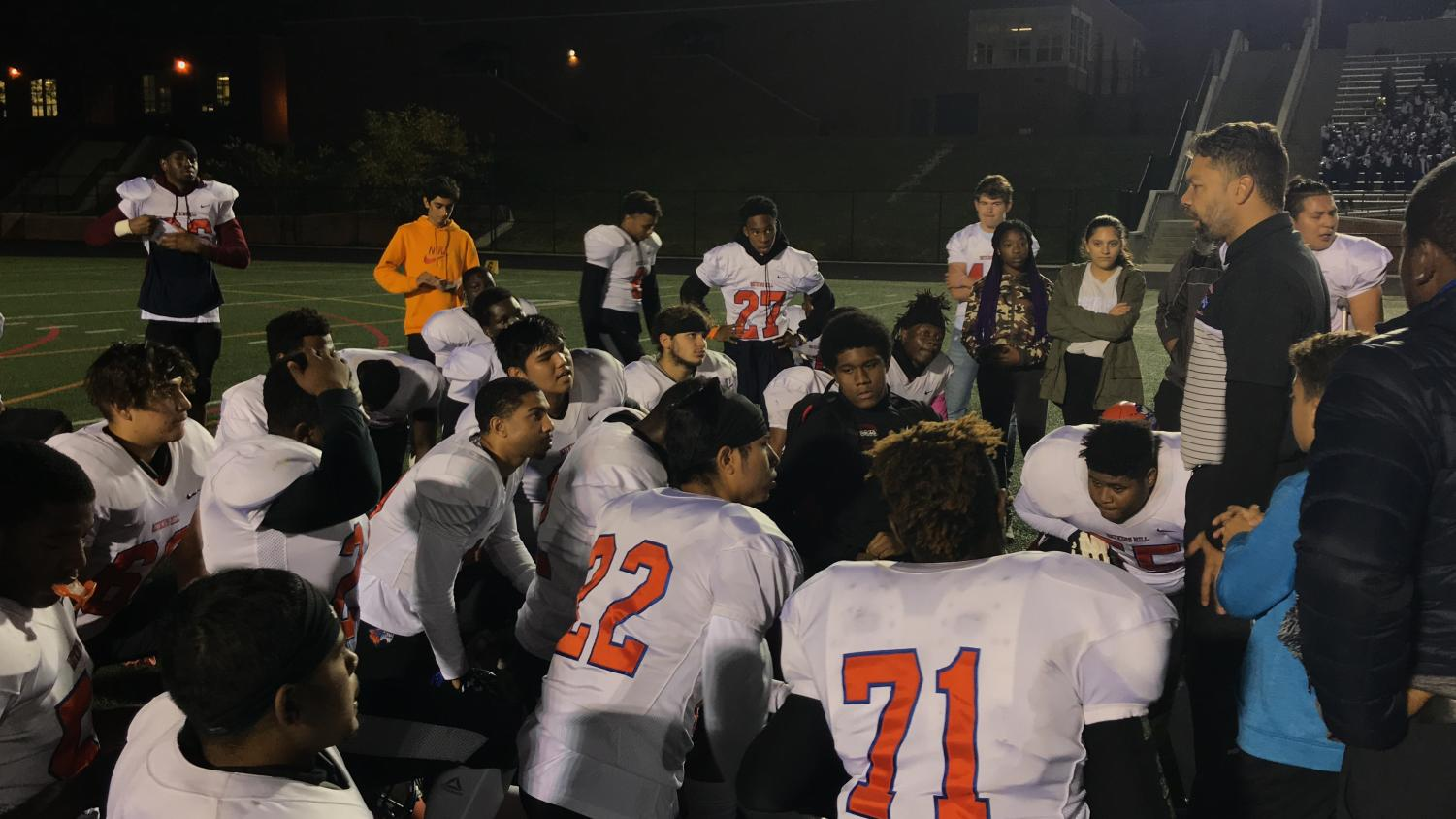 The team huddles as coach Michael Brown speaks post-win.