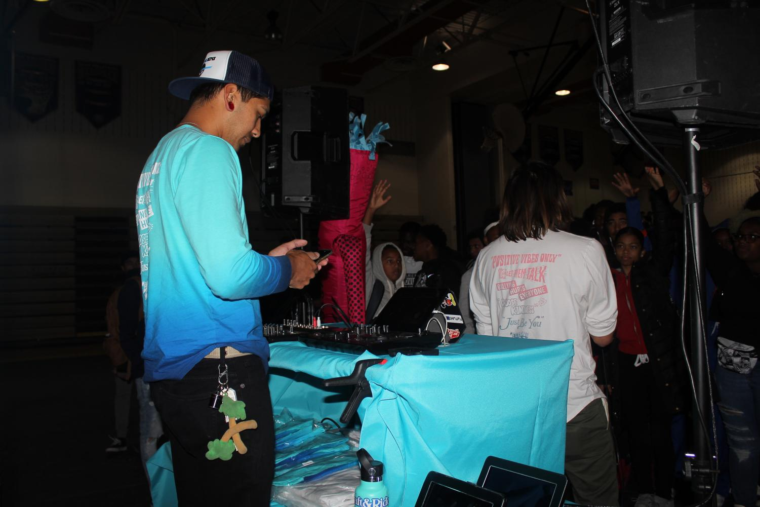 The DJ chooses music from a playlist to hype up the crowd at the event.