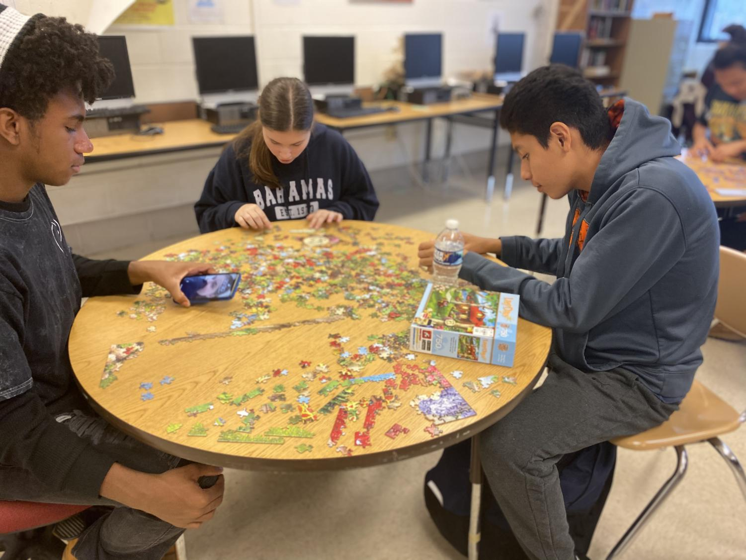Freshman Nathan Campbell, sophomore Zoe Luckabaugh, and freshman Eduardo Lezema work on a jigsaw puzzle as part of the Mental Health Day.