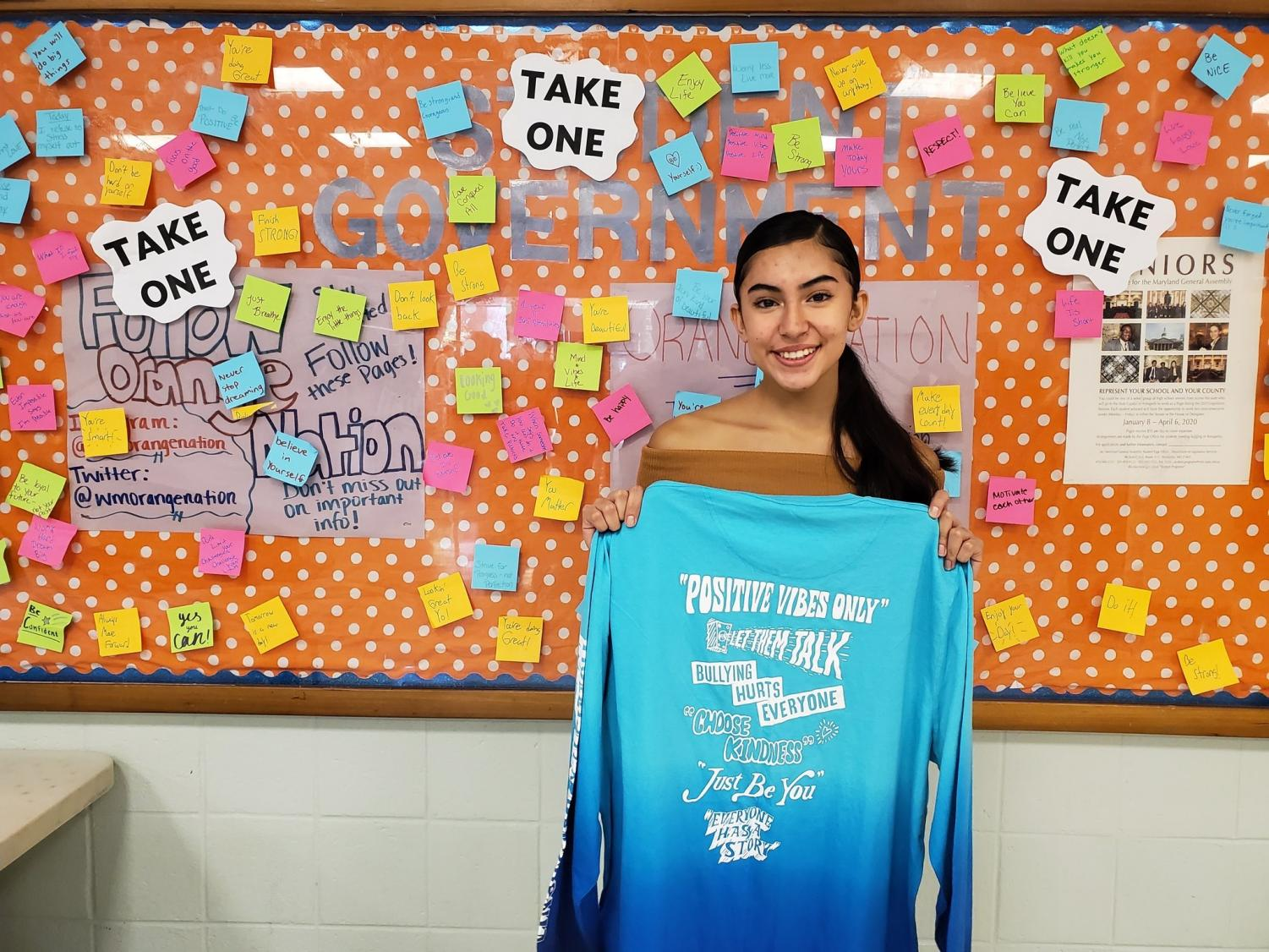 Senior Adriana Amaya stands in front of the sticky notes board in the mixing bowl. The student leadership class started putting up the positive messages as an anti-bullying campaign.