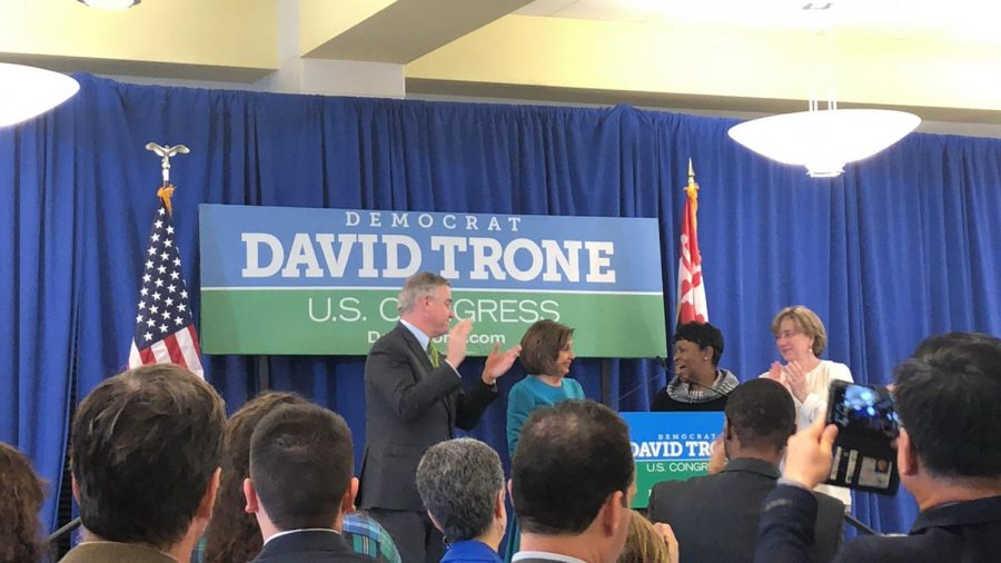 David Trone, Nancy Pelosi, and Adrienne Jones  greeting each other on stage.