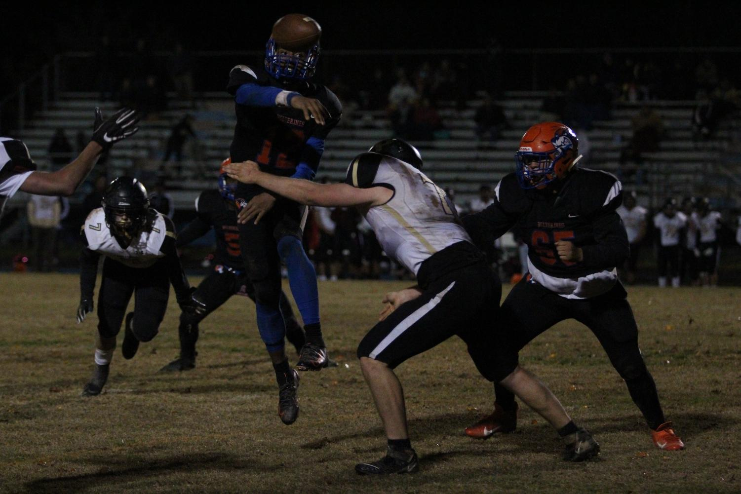 Sophomore Nehemai Cross throws the ball in midair as senior Anthony Santos moves to defend him.
