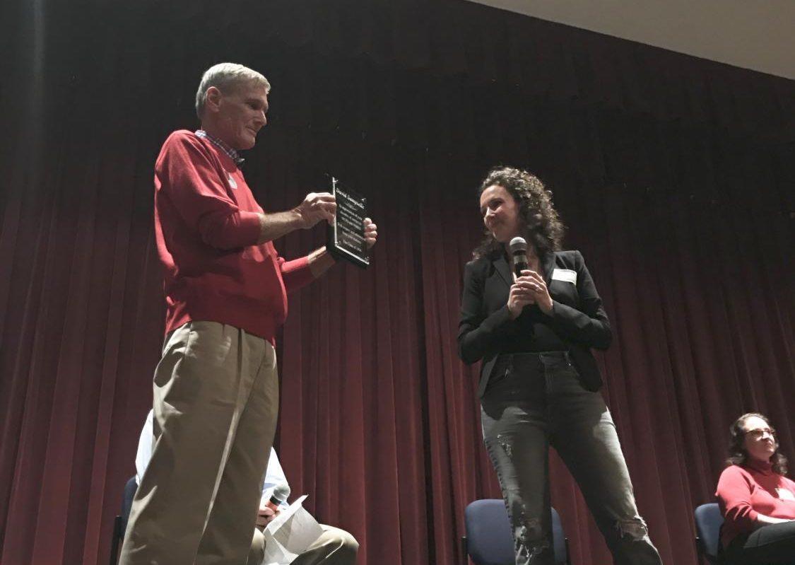 Watkins Mill alumn Jen Marchetti presents a plaque to retired teacher David Sampselle.