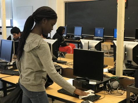 Freshman Melissa Osei-Bonsu cleans her computer keyboard with a Clorox wipe before using it in English class to protect herself from the coronavirus.