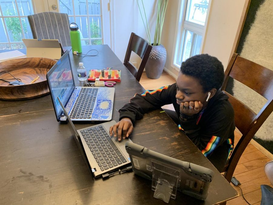 Neelsville Middle School student Aubrey Holt uses multiple devices to complete her work for her virtual classes. The majority of students in the Watkins Mill High School cluster opted to remain virtual, but about a third of students will return.