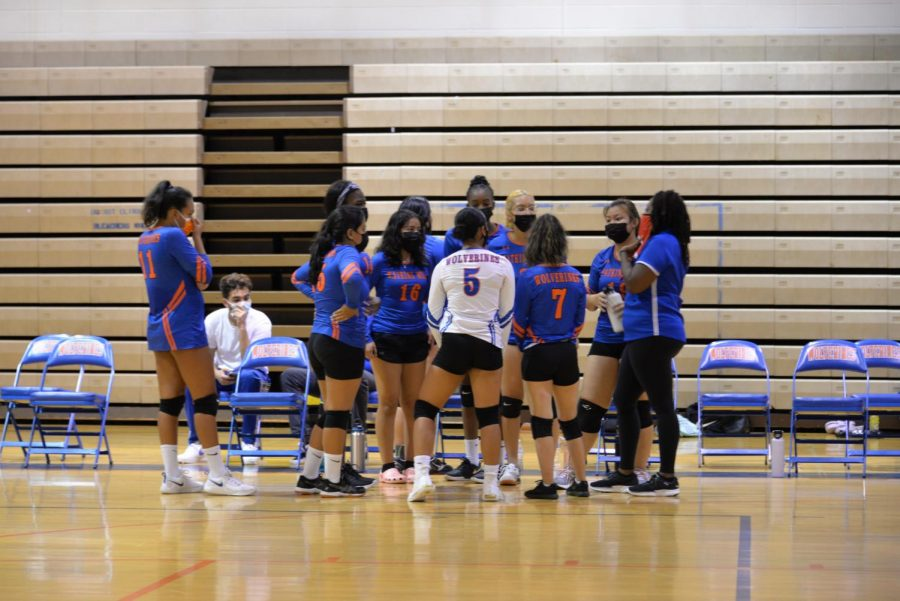 Girls volleyball huddling during a match against the Quince Orchard Cougars.